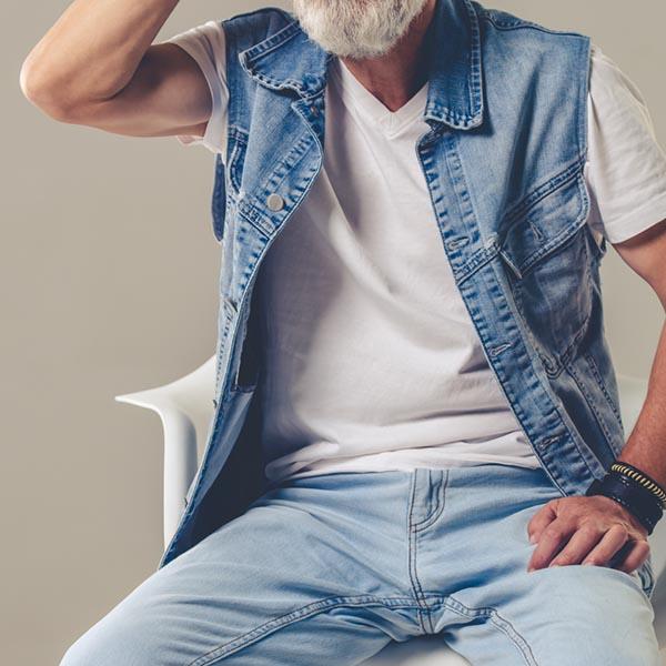 Älterer Mann sitzt auf Stuhl mit Jeans und Weste