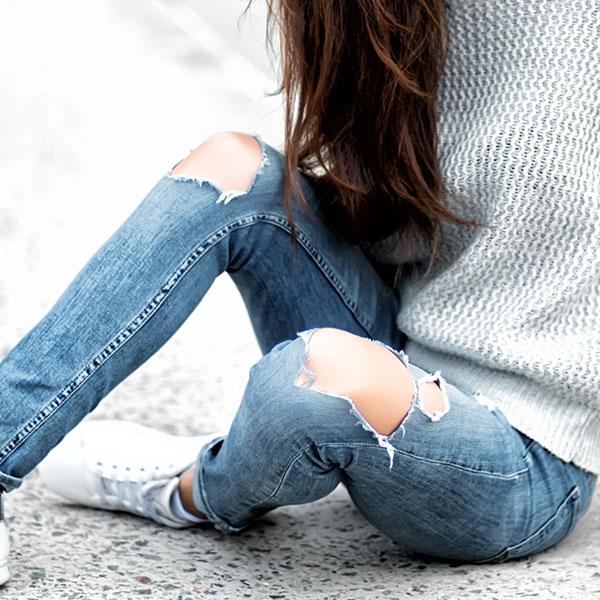 Junge Frau sitzt in Jeans auf Boden