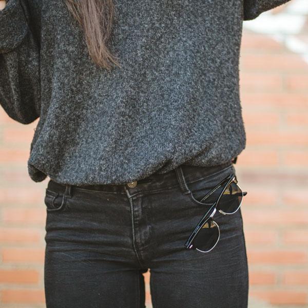 Junge Frau trägt dunkle Jeans und Sonnenbrille
